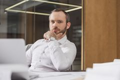 Handsome thoughtful architect sitting at workplace and looking. At camera royalty free stock photo