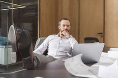 Handsome thoughtful architect sitting at workplace and looking. At laptop stock images