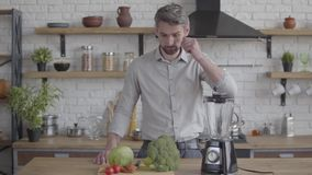 Handsome thoughtful good-looking man in the shirt standing at the table with a blender preparing to make a vegetable. A handsome good-looking man in the shirt stock video footage