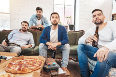 Handsome thoughtful men watching TV. Intense football match. Handsome thoughtful nice men watching an intense football match and drinking beer while resting Royalty Free Stock Photo