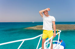 Handsome tired man standing on the yacht at a sunny summer day. Beautiful turquoise sea on background royalty free stock photography