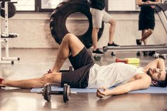 handsome tired sportsmen lying on yoga mat and resting stock images