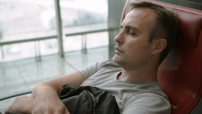 Handsome tired young man sleeping in airport terminal. Long distance connected flights jet-lag. Handsome tired young guy sleeping in chair in airport terminal stock footage