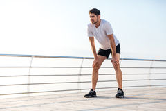 Handsome tired young sportsman standing on pier Stock Photo