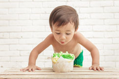 Handsome toddler in astonishment looking at sponge cake Stock Images