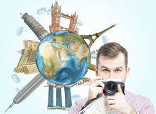 A handsome tourist with camera and a globe with sketched famous places. Light blue background. Elements of this image furnished by Stock Photo