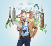 A handsome tourist in casual clothes with camera trying to find a location in the map. Drawn sketches of the most famous touristic. Places on the light blue Royalty Free Stock Photo