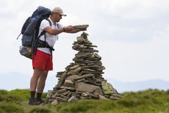 Handsome tourist man with backpack making pyramid pile of stones on lit by summer sun green grassy mountain valley on light blue c. Opy space sky background royalty free stock photography