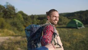 Handsome tourist man traveling in nature, holding woman`s hand. Handsome tourist man with backpack traveling in nature, holding woman`s hand on travel vacation stock video footage