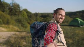 Handsome tourist man traveling in nature, holding woman`s hand. Handsome tourist man with backpack traveling in nature, holding woman`s hand on travel vacation stock footage