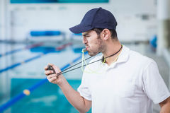 Handsome trainer blowing whistle and looking at stopwatch Stock Photography