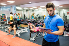 Handsome trainer using tablet in weights room Stock Photo
