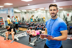 Handsome trainer using tablet in weights room Royalty Free Stock Photo