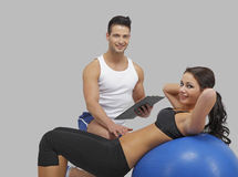 Handsome trainer with a women on ball. Handsome trainer with a female, workout on a fitness ball, on isolated grey background Stock Image