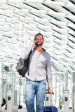 Handsome travel man talking on phone with luggage Royalty Free Stock Photo