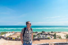 Handsome traveler man stay by blue ocean background - Happy guy relaxing at sea view point - Concept of freedom and Royalty Free Stock Image
