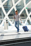 Handsome traveling man with phone and walking with suitcase Stock Photos