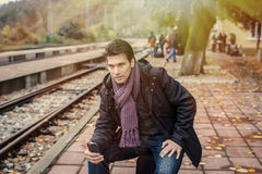 Handsome traveller with cellphone at train station Royalty Free Stock Images