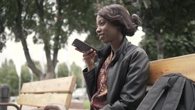 Handsome trendy african american black woman recording voice message on cell phone that he is holding, outdoor in city. Setting royalty free stock photography