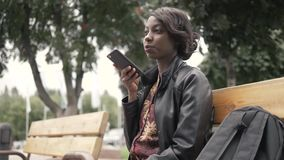 Handsome trendy african american black woman recording voice message on cell phone that he is holding, outdoor in city. Setting stock video