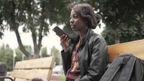 Handsome trendy african american black woman recording voice message on cell phone that he is holding, outdoor in city. Setting stock video footage