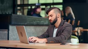 Handsome trendy male businessman chatting online using computer pc sitting on table at cafe. Medium shot. Attractive confident young man working focused looking stock video