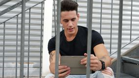 Handsome trendy man looking down at a tablet computer, outdoor. Handsome trendy man wearing t-shirt sitting and doing videochat, looking down at a tablet stock footage