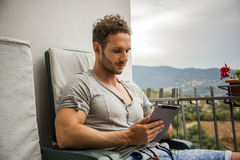 Handsome trendy man looking down at a tablet computer, outdoor Stock Photography