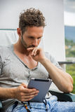 Handsome trendy man looking down at a tablet computer, outdoor Stock Photo