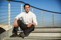 Handsome trendy man sittiing on stairs, outdoor Stock Photos