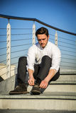 Handsome trendy man sittiing on stairs, outdoor Royalty Free Stock Photo