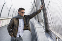 Handsome trendy man standing on a bridge, looking. Handsome trendy young man standing on a sidewalk wearing a fashionable jacket and scarf in a relaxed confident Stock Photography