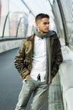 Handsome trendy man standing on a bridge Stock Photos