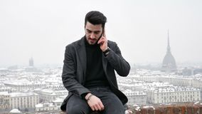 Handsome trendy man talkiing on cell phone. Handsome trendy man wearing black jacket sitting and talking on cell phone, outdoor in Turin, Italy in winter day stock video footage