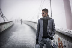 Handsome trendy man walking on a bridge in winter. Handsome trendy young man walking on a bridge in winter, carrying a metal briefcase, wearing sunglasses and Royalty Free Stock Photo