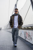 Handsome trendy man walking on a bridge in winter Royalty Free Stock Photography