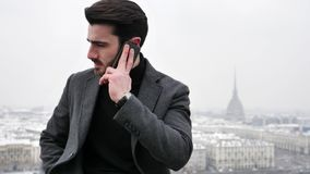 Handsome trendy man talkiing on cell phone. Handsome trendy man wearing black jacket sitting and talking on cell phone, outdoor in Turin, Italy in winter day stock video