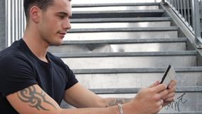 Handsome trendy man looking down at a tablet computer, outdoor. Handsome trendy man wearing t-shirt sitting and doing videochat, looking down at a tablet stock video footage