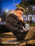 Handsome trendy young man, sitting on bench at night. Handsome trendy young man, sitting on a bench in city setting at night wearing a fashionable winter coat stock photo