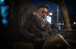 Handsome trendy young man, sitting on bench at night. Handsome trendy young man, sitting on a bench in city setting at night wearing a fashionable winter coat royalty free stock image