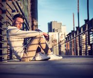 Handsome trendy young man, sitting on a sidewalk in city stock photography