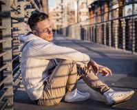 Handsome trendy young man, sitting on a sidewalk in city. Handsome trendy young man, sitting in city setting at sunset wearing a fashionable sweater or cardigan royalty free stock photography