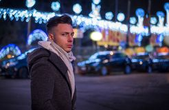 Handsome trendy young man, standing on a sidewalk at night stock image