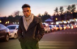 Handsome trendy young man, standing on a sidewalk at night stock images