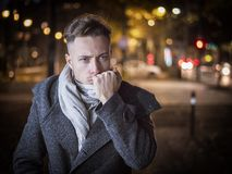 Handsome trendy young man, standing on a sidewalk at night. Handsome trendy young man, standing on a sidewalk in city setting at night wearing a fashionable royalty free stock image