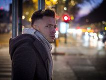 Handsome trendy young man, standing on a sidewalk at night. Handsome trendy young man, standing on a sidewalk in city setting at night wearing a fashionable royalty free stock photos