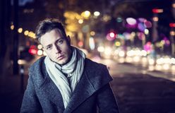 Handsome trendy young man, standing on a sidewalk at night. Handsome trendy young man, standing on a sidewalk in city setting at night wearing a fashionable stock images