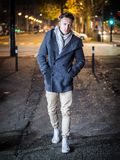 Handsome trendy young man, standing on a sidewalk at night. Handsome trendy young man, standing on a sidewalk in city setting at night wearing a fashionable stock photo