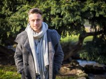 Handsome trendy young man, walking in city park stock photo