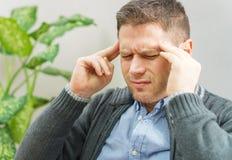 Man having a headache. Handsome unshaved man having a headache at home stock photos